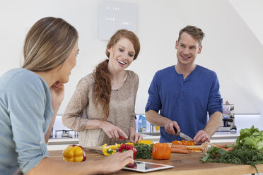Three friends preparing meal and using tablet computer - RBF001497