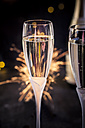 Champagne flutes in front of fireworks, close-up - SBDF000454