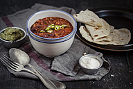 Tortillas and bowls of guacamole, sour cream, Chili con carne on wooden table - SBDF000443