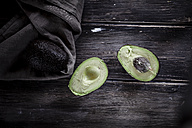 Sliced and whole avocados on chopping board and wooden table - SBDF000463