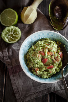 Bowl of guacamole, kitchen towel, pestle, sliced lime and hollowed half of avocado on wooden table - SBDF000471