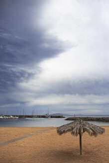Portugal, Madeira, Machico, Yellow beach with beach umbrella, view to harbour - VT000061