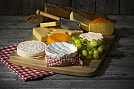 Cheese platter, different cheese, french cheddar, french soft cheese, french sheep cheese, camembert, emmentaler, and austrian mountain cheese and wholemeat baguette on wooden board - MAEF007646