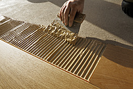 Man applying glue for laying finished parquet flooring, close-up - BIF000300