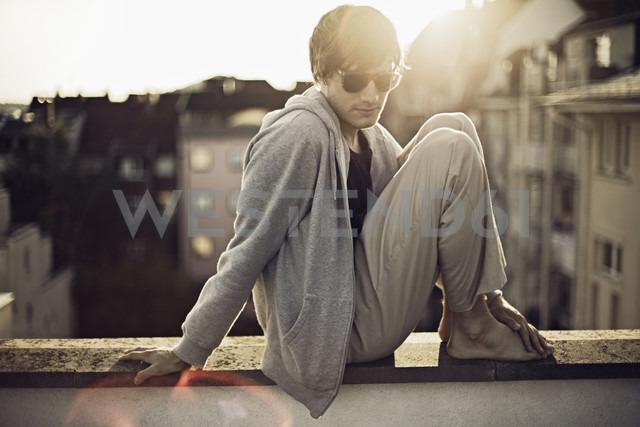 Germany, Baden-Wuerttemberg, Pforzheim, young man sitting on wall - DW000170