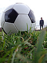 Cologne, North Rhine-Westphalia, Germany, football lying in the grass, young man in the background - JATF000620