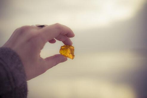 Germany, Mecklenburg-Western Pomerania, Ruegen, Hand holding amber - MJF000716