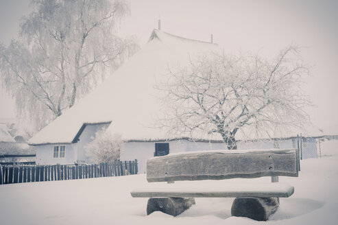 Germany, Mecklenburg-Western Pomerania, Ruegen, Empty bench at Pfarrwitwenhaus Gross Zicker in winter - MJ000610