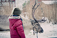 Germany, Mecklenburg-Western Pomerania, Ruegen, Boy with reindeer in winter - MJ000598