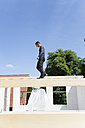 Construction of a residential house, man walking on wooden beam - FKF000376