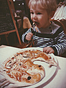 Toddler eating a dragon or fish pizza at a restaurant, Bonn, NRW, Germany - MFF000774