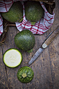Sliced and whole round courgettes, kitchen towel and a pocket knife on dark wooden table - LVF000480