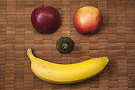 Funny fruit face with banana, cucumber, and apple on wooden table, close up - ZMF000139