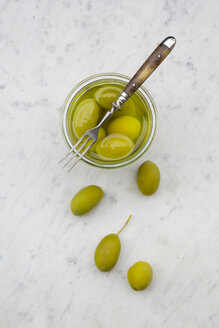 Preserving jar of pickled green olives and a fork on white marble, elevated view - LVF000477