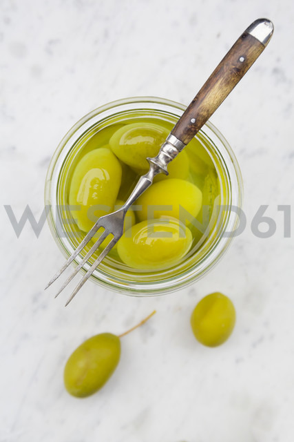 Preserving jar of pickled green olives and a fork on white marble, elevated view - LVF000476