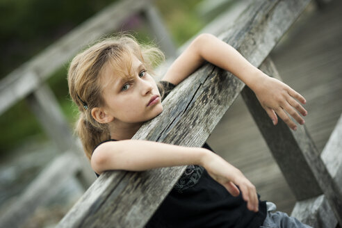 Portrait of serious looking girl at wooden boardwalk - PAF000273