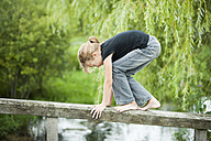 Girl balancing on railing of wooden boardwalk - PAF000271
