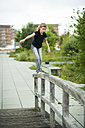 Girl balancing on railing of wooden boardwalk - PAF000275