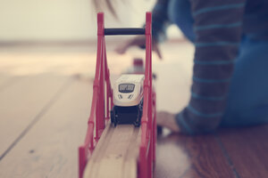 Little girl playing with wooden railroad, partial view - LV000497