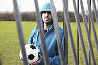 Young man with football leaning at goalpost - JATF000593