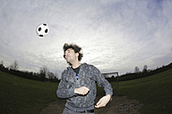 Young man heading a football - JATF000631