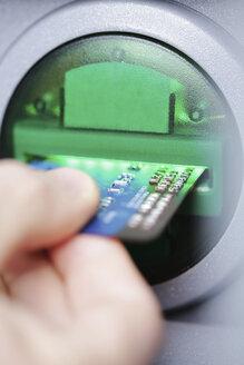 Man pushing credit card at cash dispenser, close-up - JATF000599