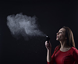 Young woman blowing powder of make-up brush - BFRF000324