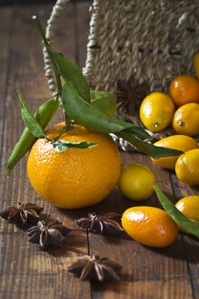 Tangerine (Citrus reticulata), kumquats and star anise (Illicium verum) on wooden table - YFF000003