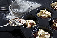 Raw muffin dough in muffin tray, spoon and strainer, close-up - YFF000008