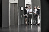 Businesspeople talking at elevator - CHAF000038