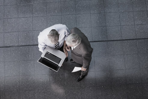 Two businessmen with laptop in office lobby - CHAF000036