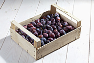 Wooden box with plums on wooden table - CSF020727