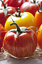 Different tomatoes on wood wool and wooden table - CSF020722