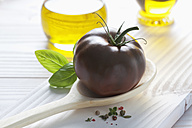 Black tomato on wooden spoon, olive oil, basil and peppercorns on wooden table - CSF020716