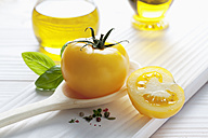 Yellow tomato on wooden spoon, olive oil, basil and peppercorns on wooden table - CSF020676