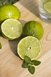 Sliced and whole limes and glass on wooden table - YFF000013