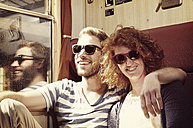 Portrait of young couple with wooden sunglasses sitting in compartment - HOHF000408