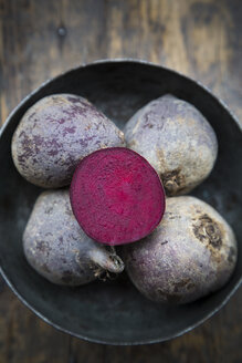 Bowl of whole beetroots and a half on wooden table - LVF000503