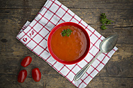 Bowl of tomato soup on kitchen towel and wooden table - LVF000508
