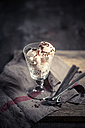 Glass of vanilla icecream with chocolate granules, spoons and kitchen towel on wood - SBDF000510