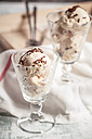 Two glasses of vanilla icecream with chocolate granules and kitchen towel on wood - SBDF000512