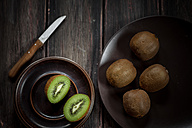 Plates of whole and sliced kiwi fruits and a knife on wooden table - SBDF000490