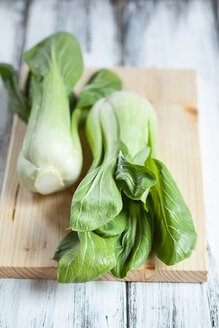 Two Chinese cabbages and a kitchen board on wooden table - SBDF000501