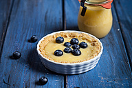 Lemon tart decorated with blueberries and glass of lemon curd on blue wooden table - SBDF000526