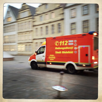 Ambulance passing quickly through pedestrian zone. With motion blur. Alter Markt, Bielefeld, Germany - ZM000175