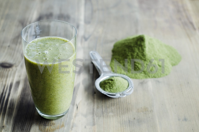 Moringa powder on spoon and wooden table and glass of moringa smoothie - CZF000133