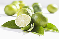 Limes and leaves on wooden table - CSF020741
