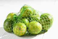 Limes in net on wooden table - CSF020744