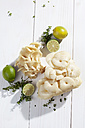 Golden Oyster Mushrooms (Pleurotus citrinopileatus), limes, and lemon thyme on wooden table - CSF020753