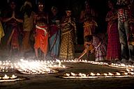 India, Uttar Pradesh, Varanasi, Maha Shivaratri, a woman lighting a oil lamp - JBA000050